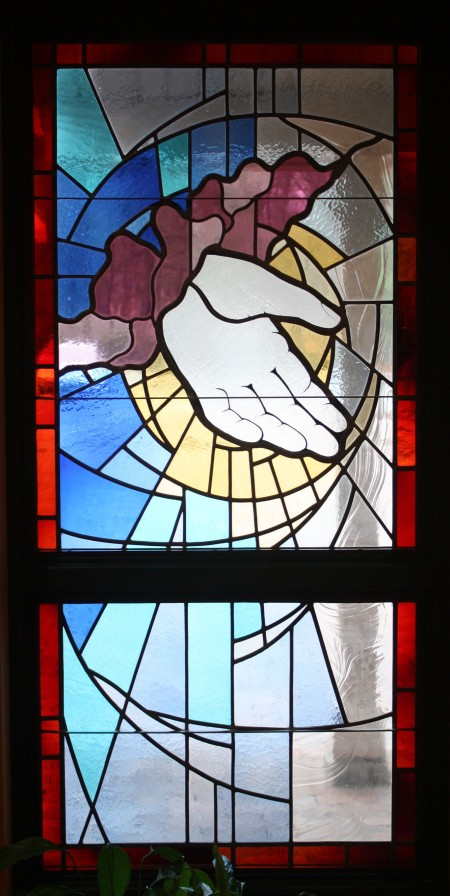 The hand of God stained glass in the narthex